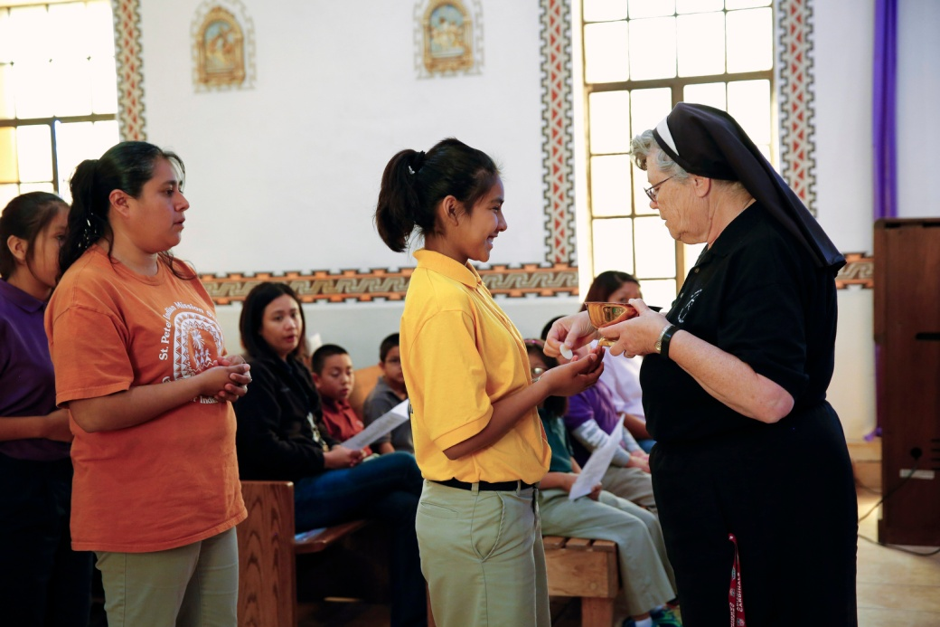 Franciscan sister distributes Communion during weekday Mass at St. Peter Indian Mission School in Arizona